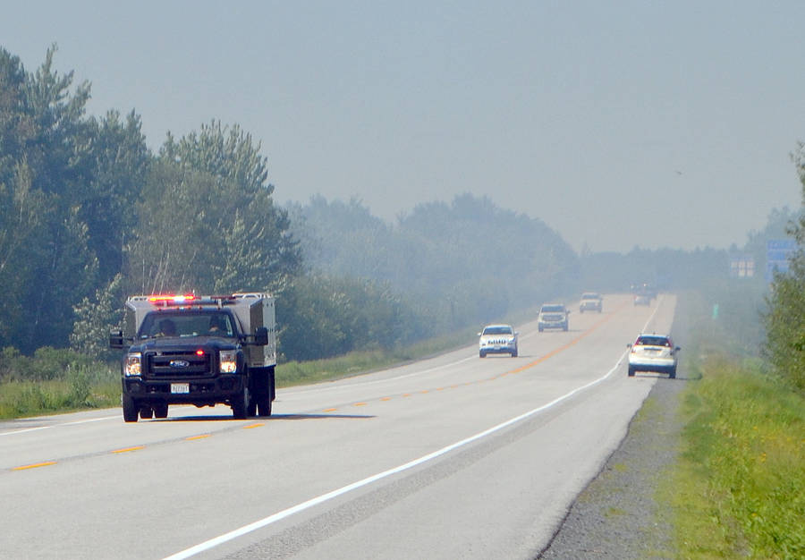 <p>KEITH CORCORAN, PHOTO</p><p>A Department of Lands and Forestry fire response vehicle on Highway 103 heading to the Hebbville fire scene Tuesday. A smokey haze is seen over the road.</p>
