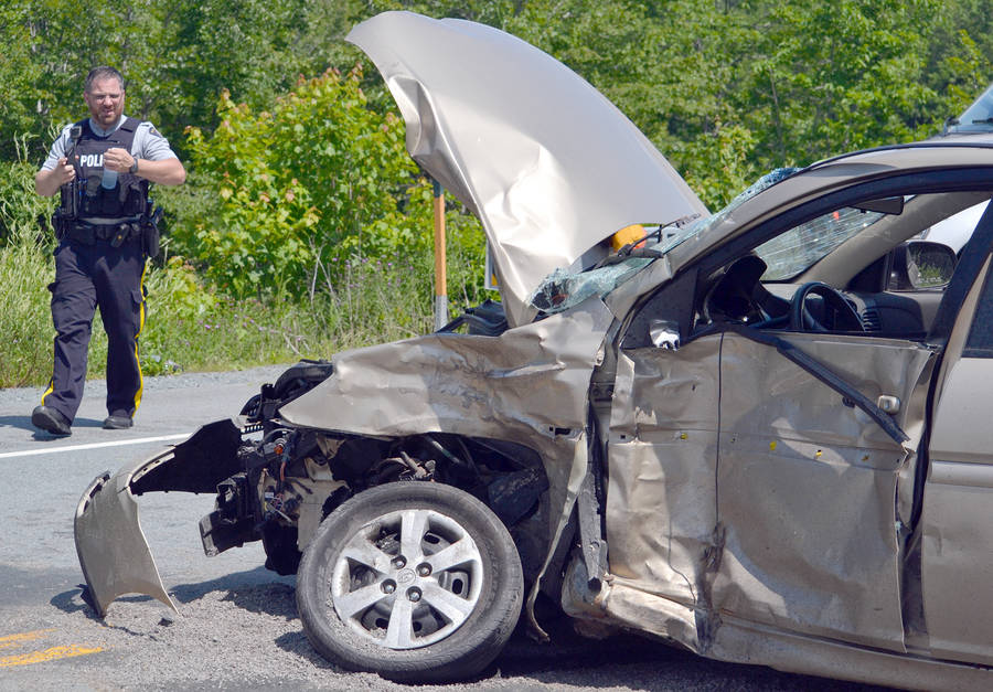 <p>KEITH CORCORAN, PHOTO</p><p>A RCMP officer walks in the area where a Hyundai Accent, pictured, collided on Highway 103 with an Audi Q5 Quattro sport utility vehicle July 20.</p>