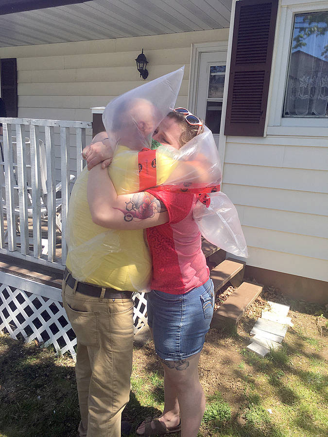<p>CONTRIBUTED PHOTO</p><p>Samantha Green gives her father an emotional but protected hug, the first time they&#8217;ve been able to do that since the pandemic began.</p>