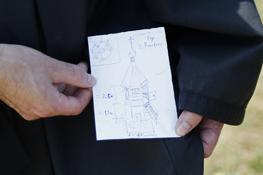 <p>BRITTANY WENTZELL PHOTO</p><p>Father Cassian holds up a drawing by Andrei Diachkov of a possible tower for the bells. First the monks will have to generate the funds and find someone who can build in that style.</p>