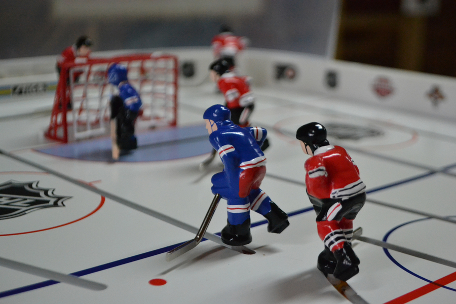 <p>EVAN BOWER PHOTO</p><p>Tiny players on the tabletop hockey board move back and forth on slots via metal rods.</p>