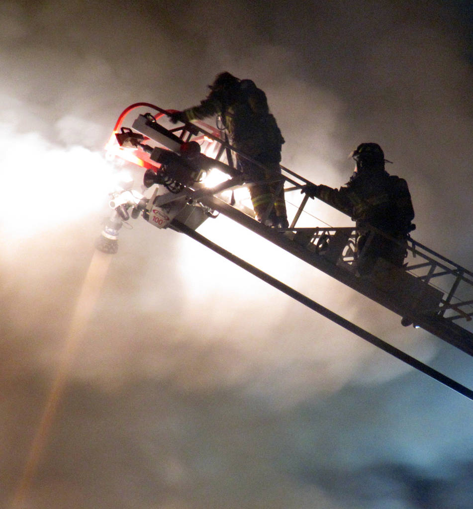 <p>KEITH CORCORAN PHOTO</p><p>Firefighters deal with smokey conditions from high above on a ladder truck.</p>