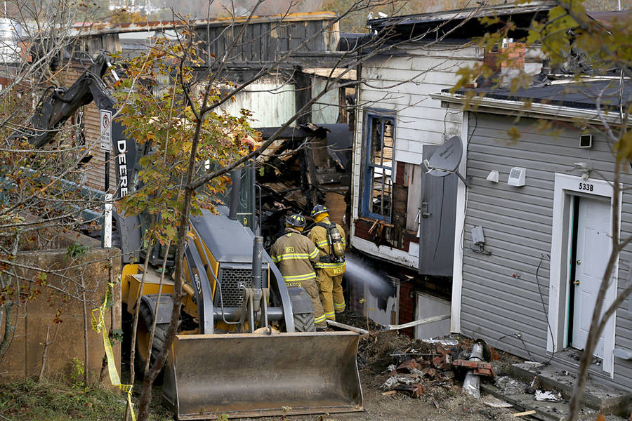 <p>BRITTANY WENTZELL PHOTO</p><p>Volunteer firefighters putting out hot spots in the back of one of the buildings damaged in the Sunday night fire.</p>