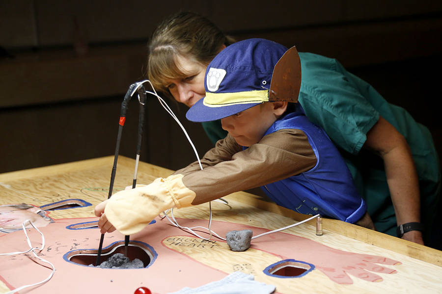 <p>Kyson Comeau plays a game of Operation with the help of teacher Liz Clark.</p>