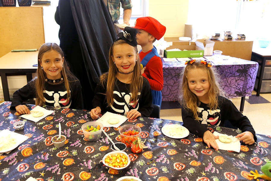 <p>Aliyah Demne, Kelsi-Rose Tanner, and Ivy-Marie Tanner decorate cookies together, all dressed as skeletons.</p>