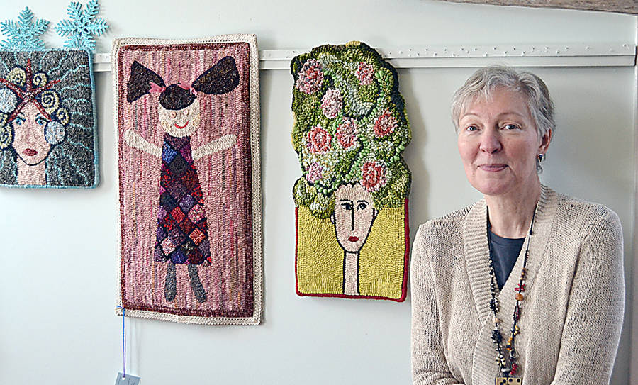 <p>Jane Steele among some of her favorite rug hook designs at her shop in Petite Rivière.</p>