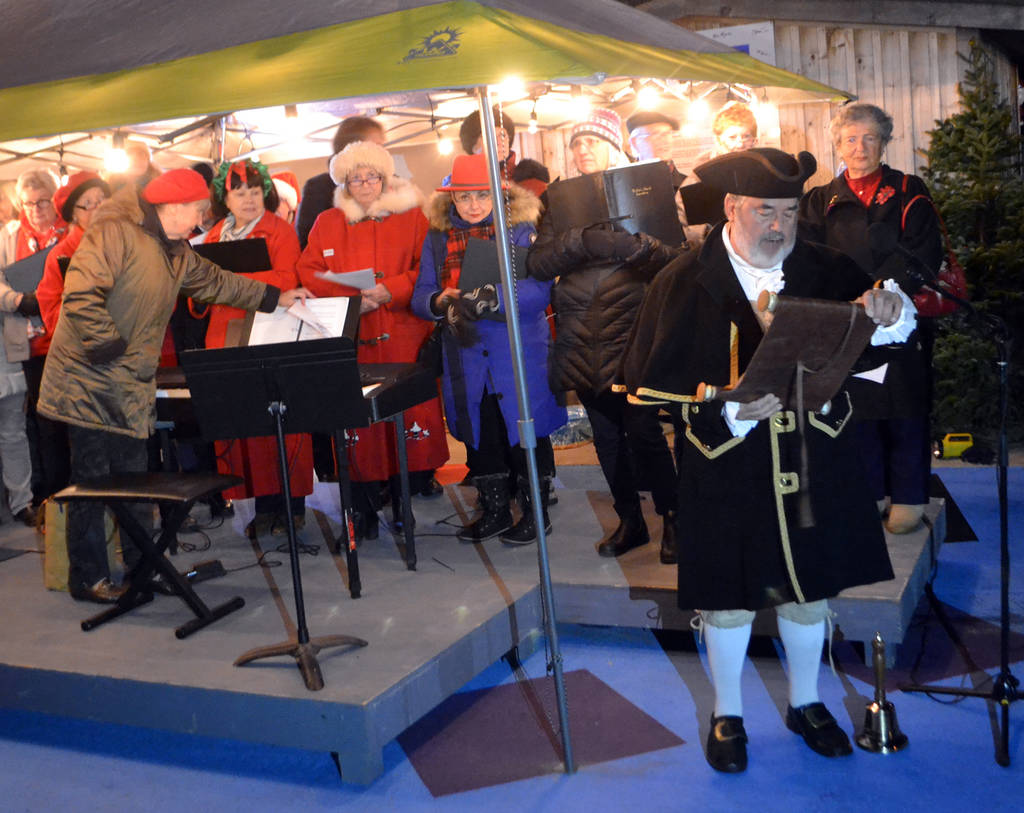 <p>Town crier John McGee, with carollers behind him, welcomes people to the lighting of the vessels.</p>