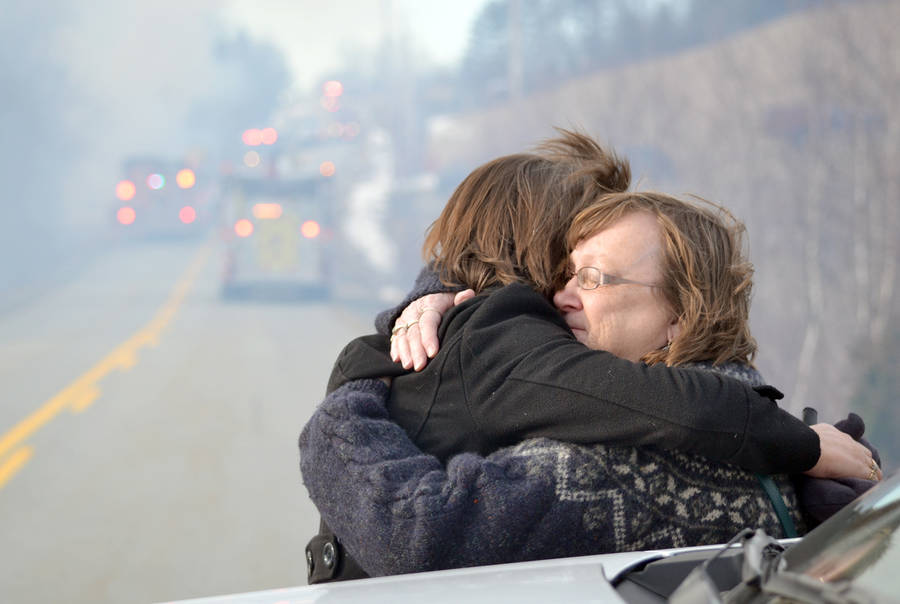 <p>KEITH CORCORAN PHOTO</p><p>Two women, believed to know a person who lives in the fire-damaged home, embrace near the scene.</p>