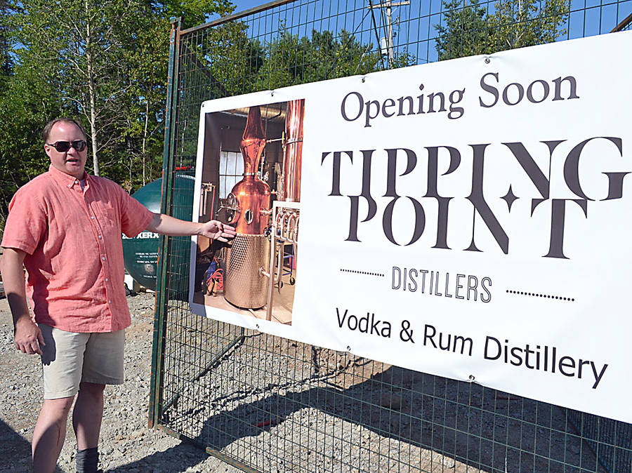 <p>GAYLE WILSON PHOTO</p><p>David Blackburn points to the sign on the gate of the construction site of his new distillery, Tipping Point, which carries an image of the type of high-end copper still the facility will feature.</p>