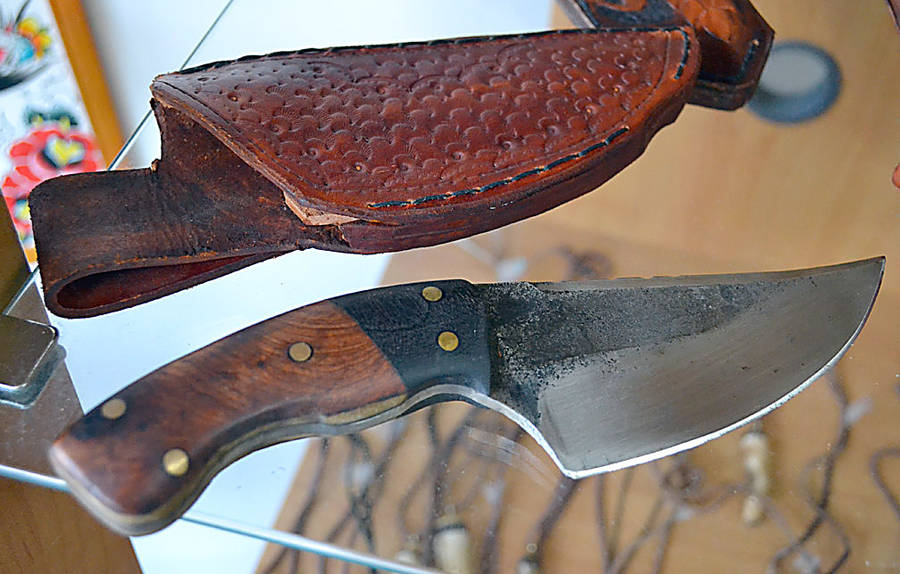 <p>Knives and hand-crafted pouches by Mike Power sells alongside his tattoo and barbershop service.</p>
